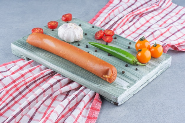 Verse salami en groenten op houten plaat.
