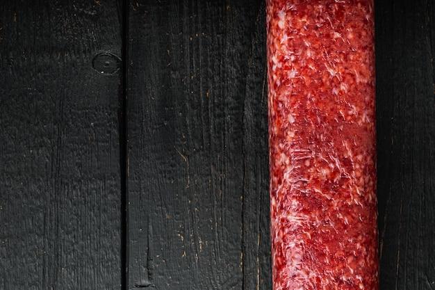 Verse salami set, op zwarte houten tafel, bovenaanzicht plat gelegd