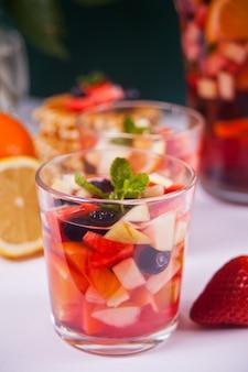 Verse sangria van rode wijn of punch met fruit en bessen.