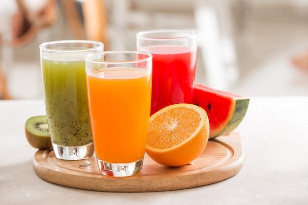 Verse sappen smoothie drie glazen rood groen oranje tropisch fruit