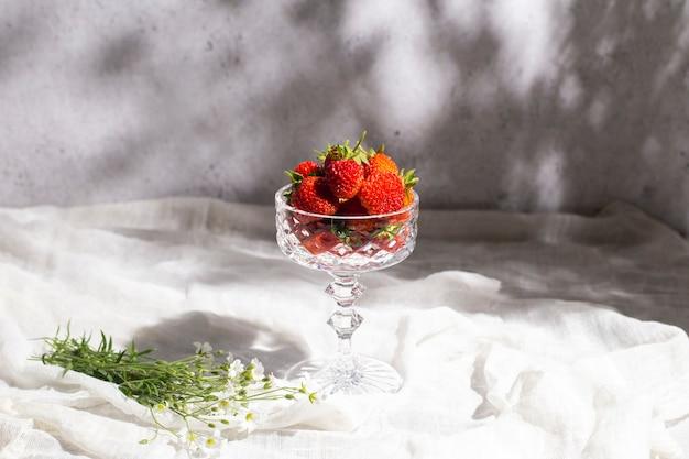 Verse, sappige aardbeien in een glas, een boeket wilde bloemen op een tafel op een betonnen achtergrond.