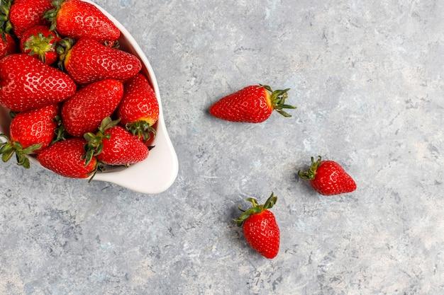 Verse, sappige aardbeien op lichte muur, bovenaanzicht