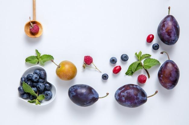 Verse, sappige bessen en fruit op een wit bord.