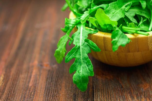 Verse, sappige bladeren van rucola op een bruine houten tafel.