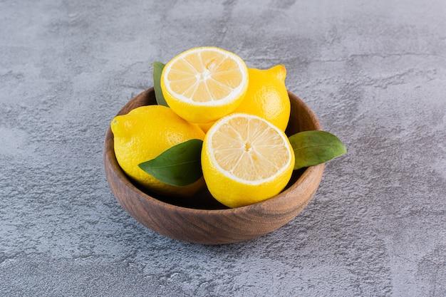 Verse, sappige citroenen in houten kom.