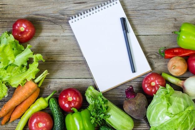 Verse, sappige groenten grens, lege witte kladblok