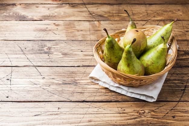 Verse, sappige peren conferentie in een mand op een houten rustieke achtergrond.