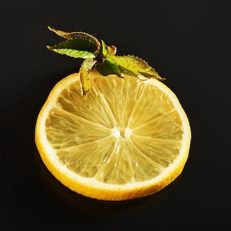 Verse, sappige plakjes citroen op een zwarte.