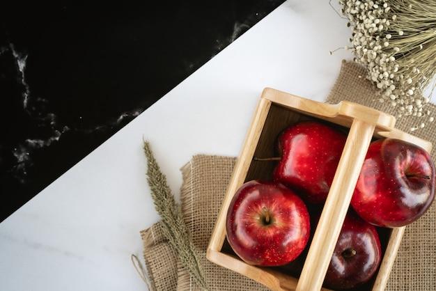 Verse, sappige rode appels in houten mand op een zak en zwart-wit marmeren oppervlak met tarwegras en een bos gras