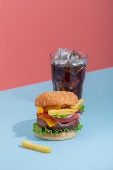 Verse, sappige rundvleeshamburger die op creatieve blauwe achtergrond, isometrische verticale oriëntatie wordt geplaatst