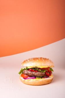 Verse, sappige rundvleeshamburger die op creatieve oranje achtergrond met exemplaarruimte wordt geplaatst, isometrische verticale oriëntatie