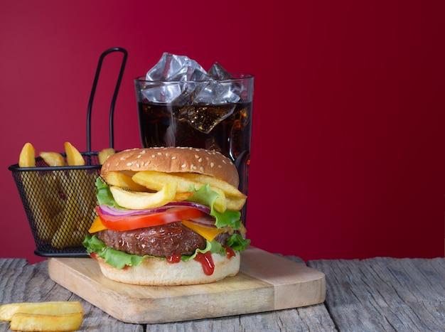 Verse, sappige rundvleeshamburger met frietjes en cola die op houten achtergrond met exemplaarruimte wordt geplaatst