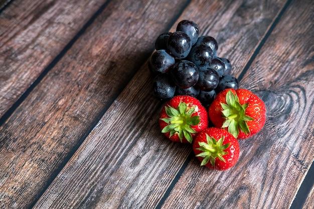 Verse schotse aardbeien en zwarte druiven bovenop houten lijst.