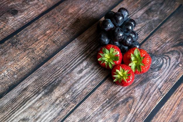 Verse schotse aardbeien en zwarte druiven bovenop houten lijst