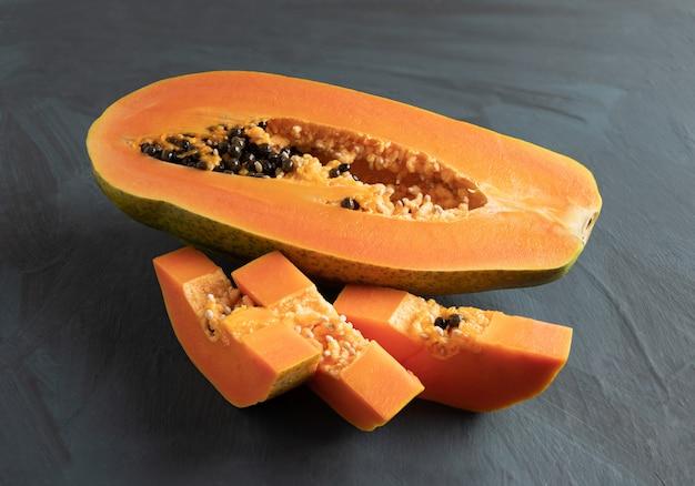 Verse seizoensgebonden papaja geïsoleerd van rustieke achtergrond