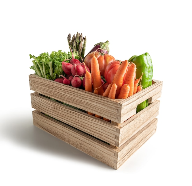 Verse seizoensgroenten in houten kist, geïsoleerd op een witte achtergrond
