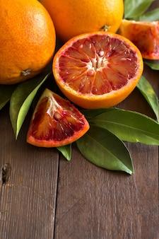 Verse siciliaanse sinaasappelen met bladeren op een houten tafel