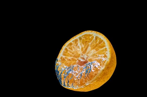 Verse sinaasappel die in water met plons op zwarte achtergrond valt