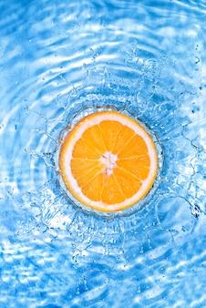 Verse sinaasappel in het water gevallen met bubbels op wit wordt geïsoleerd
