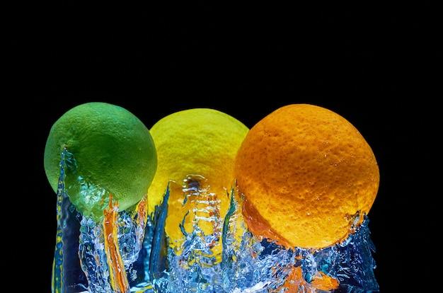 Verse sinaasappel, lyme, citroen die in water met plons op zwarte achtergrond valt