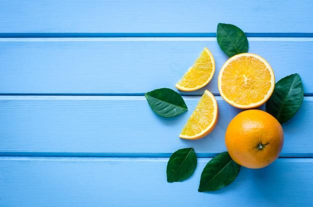 Verse sinaasappelen en sap op het blauwe hout