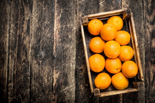 Verse sinaasappelen in doos op een houten achtergrond