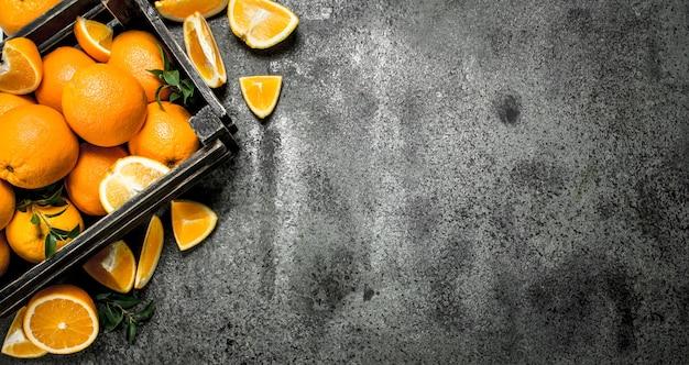 Verse sinaasappelen in een doos op een rustieke achtergrond