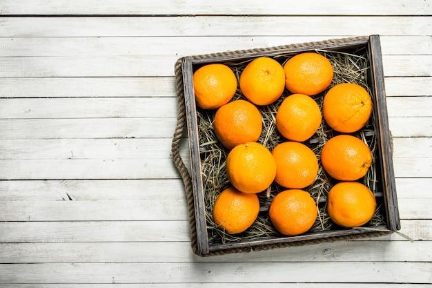 Verse sinaasappelen in een doos op een witte houten tafel