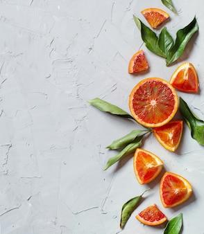 Verse sinaasappelen met bladeren op een oude tafel