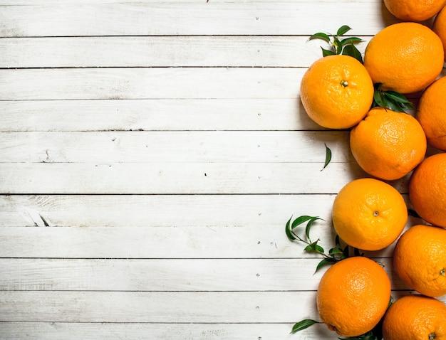 Verse sinaasappelen met bladeren op een witte houten tafel