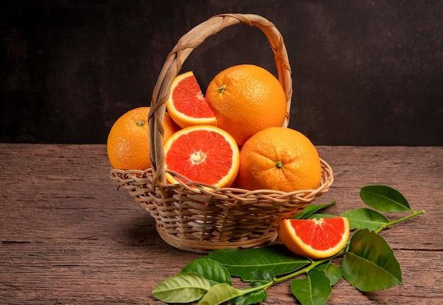 Verse sinaasappelen met sinaasappelschijfjes op houten achtergrond grapefruit of cara cara sinaasappel met bladeren