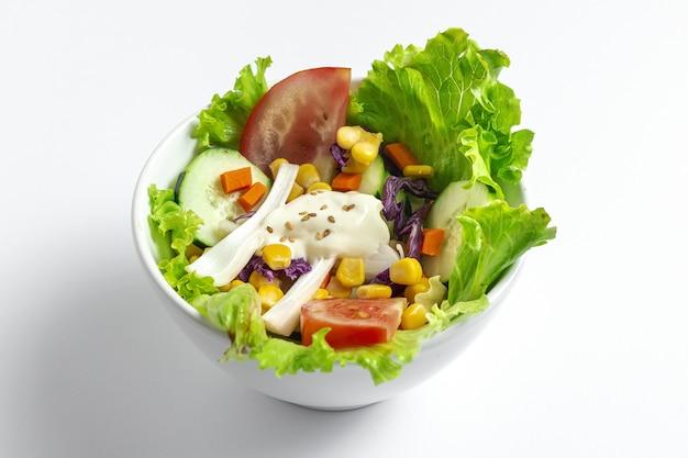 Verse sla salade met tomaten, rode ui, maïs, wortelen, komkommer