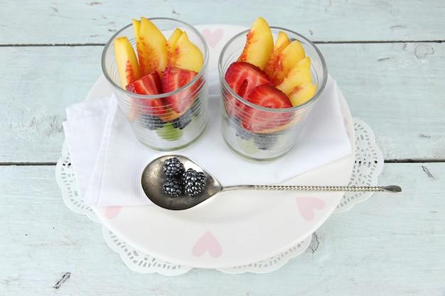 Verse smakelijke fruitsalade op blauwe houten tafel