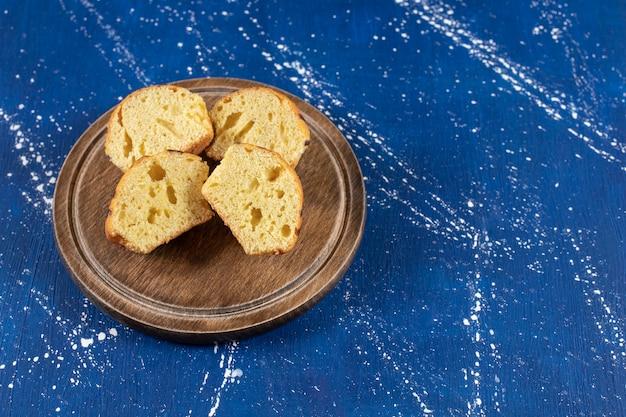 Verse smakelijke gesneden taarten geplaatst op houten plaat