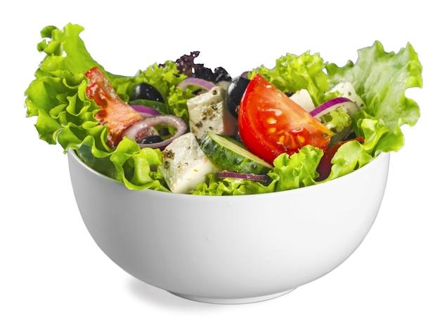 Verse smakelijke groentesalade in kom op witte achtergrond