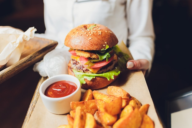 Verse smakelijke hamburger en friet op houten tafel.