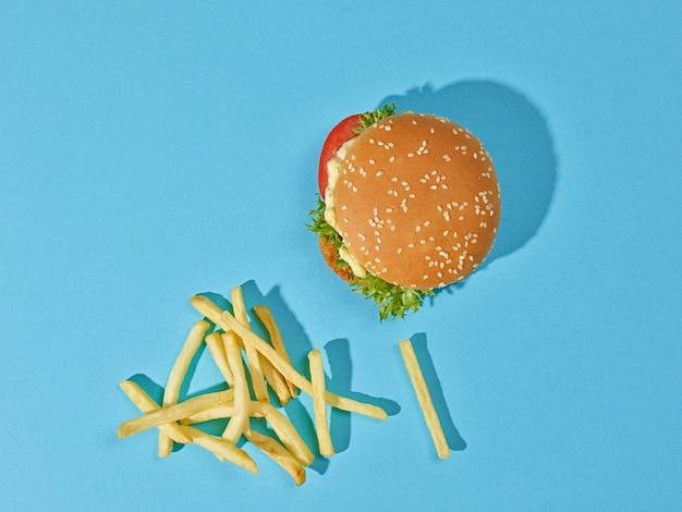 Verse smakelijke hamburger en frietjes op blauwe achtergrond van papier, bovenaanzicht