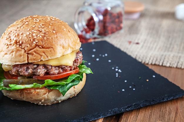 Verse smakelijke hamburger met kaas, sla, tomaat, komkommer op zwarte steen met saus. amerikaans fastfood. cheeseburger met kopie ruimte op houten achtergrond. close-up, selectieve aandacht. voedsel. grill menu