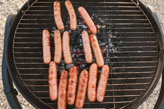 Verse smakelijke hotdogs, sappig van binnen met kleine char aan de buitenkant buiten grillen voor strandfeest