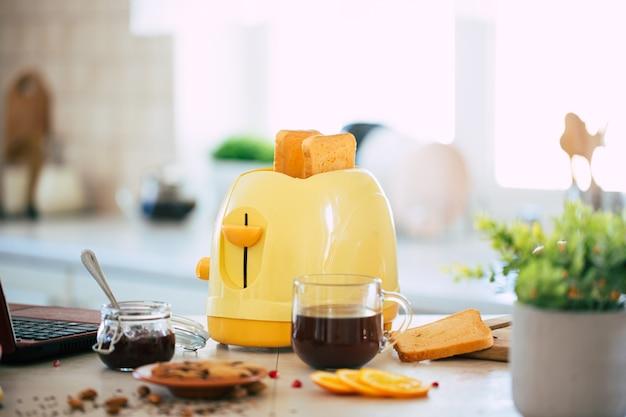 Verse smakelijke sneetjes toast uit de gele broodrooster op de mooie keukentafel thuis