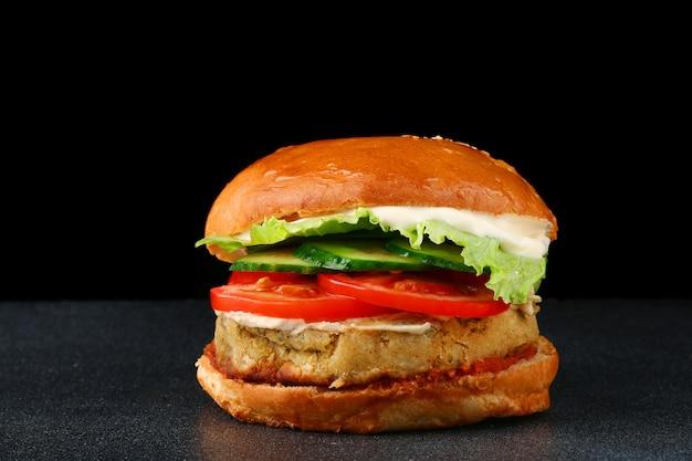 Verse smakelijke vegan hamburger op zwarte geïsoleerde achtergrond. tomaat, ui, vegan mayonaise. veganistische kikkererwtenburgers met gepekelde komkommers