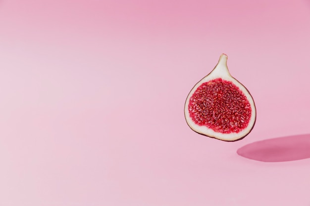 Verse smakelijke vijgenfruit halve levitatie met schaduw op roze achtergrond. dwarsdoorsnede van vijg die naar beneden valt of vliegt. veganistisch woestijnconcept. schaduw van vliegend gezond eten. kleurrijke foto van hoge kwaliteit