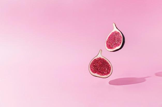 Verse smakelijke vijgenfruit helften levitatie met schaduw op roze achtergrond. twee dwarsdoorsneden van vijgen vallen of vliegen. veganistisch woestijnconcept. schaduw van vliegend gezond eten. hoge kwaliteit foto