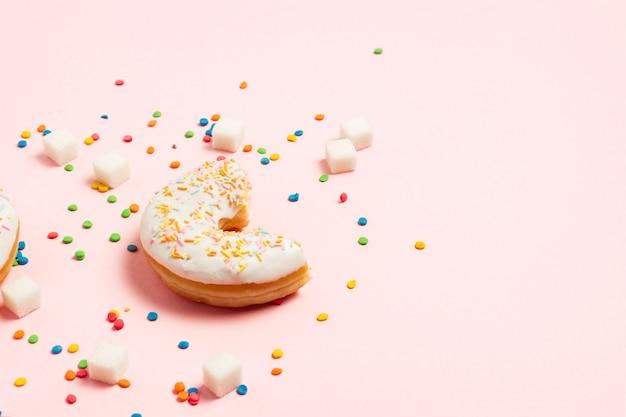 Verse smakelijke zoete donut op een roze achtergrond. bakkerijconcept, vers gebak, heerlijk ontbijt, fastfood, coffeeshop. plat lag, bovenaanzicht.