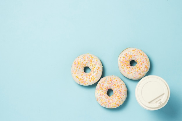 Verse smakelijke zoete donuts en een papieren kopje koffie of thee op een blauwe achtergrond. snel voedselconcept, bakkerij, ontbijt ,.