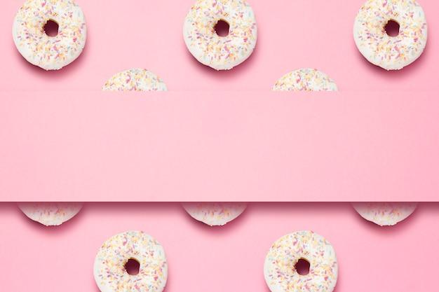 Verse smakelijke zoete donuts op een roze achtergrond. plaats voor tekst. concept van fast food, bakkerij, ontbijt, snoep. minimalisme. patroon.