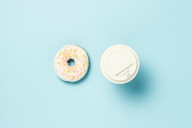 Verse smakelijke zoete doughnut en document kop met koffie of thee op een blauwe achtergrond. snel voedselconcept, bakkerij, ontbijt ,. minimalisme. plat lag, bovenaanzicht.