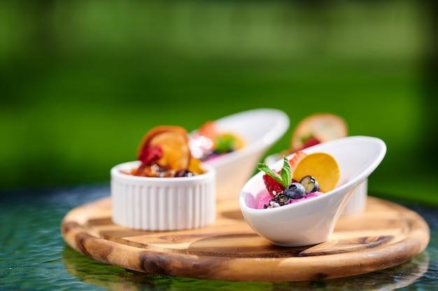 Verse snacks met aardbeien, bosbessen, ijs, munt, gedroogde sinaasappel op een houten bord