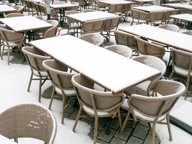 Verse sneeuw op de tafels en stoelen van openluchtrestaurant