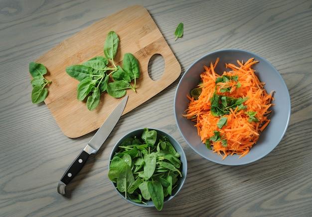 Verse spinazie ligt op een snijplank. op een houten tafel staat een keukenmes, een kom met geraspte wortelen en een kom met spinazie.